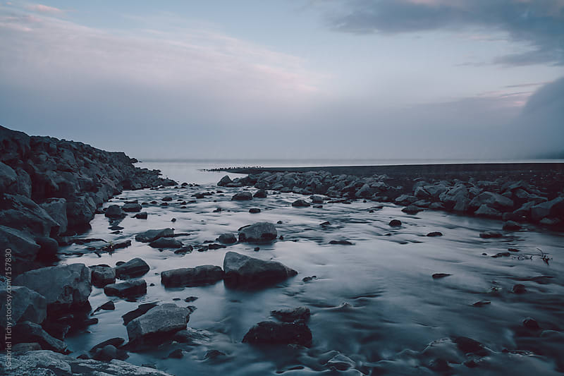 Rocky shore with black sand beach by Gabriel Tichy for Stocksy United