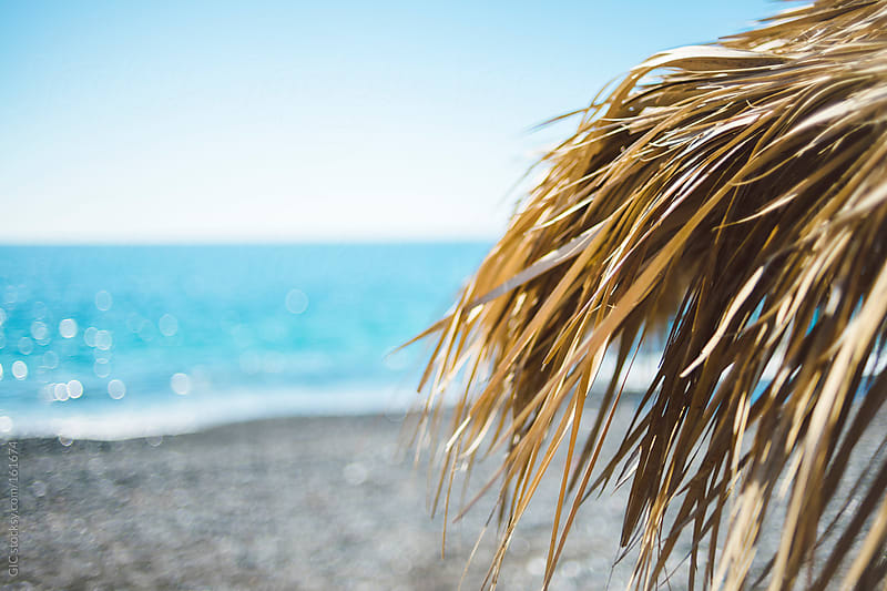Straw beach umbrella in Santorini by GIC for Stocksy United