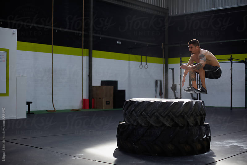 Fit man jumping over two big tires by Miquel Llonch for Stocksy United