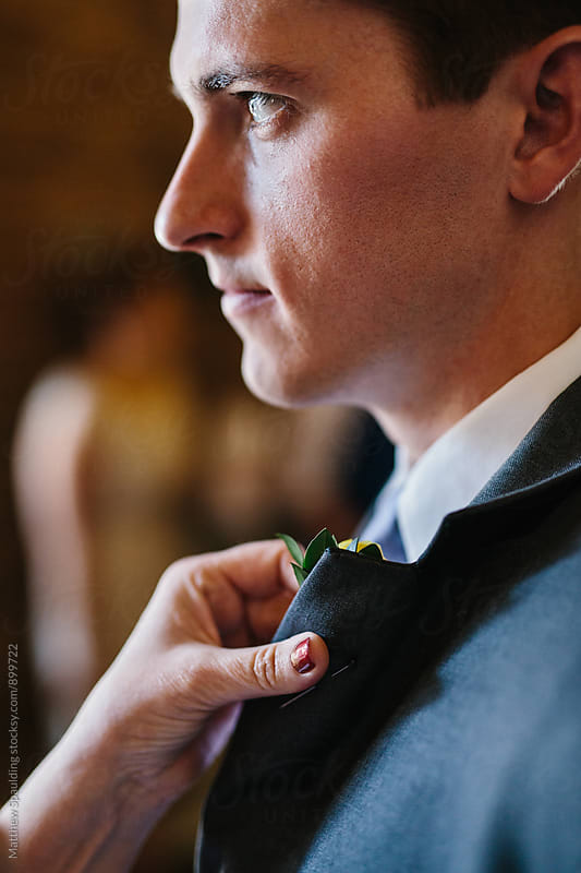 Best man in wedding having corsage pinned to lapel by Matthew Spaulding for Stocksy United