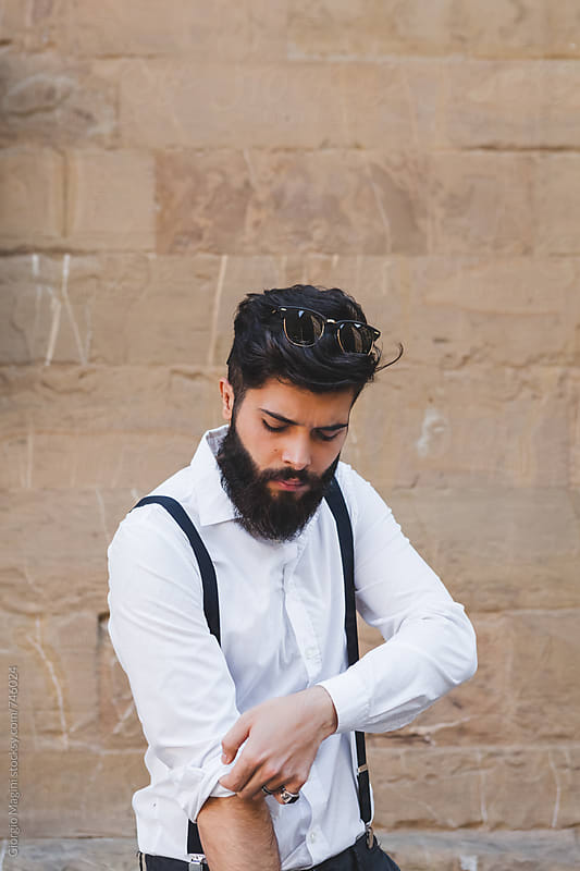 Bearded Young Man Rolling Up the Sleeves of his White Shirt by Giorgio Magini for Stocksy United