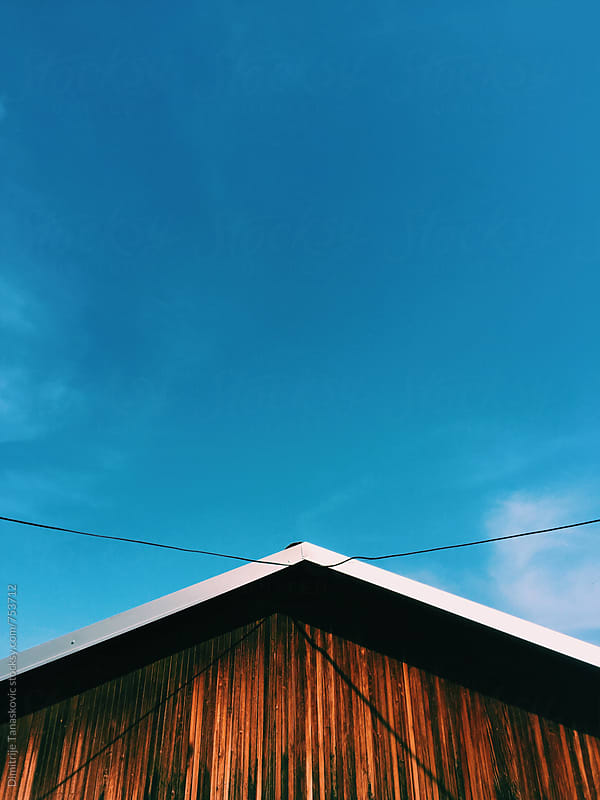 House roof under the clear blue sky by Dimitrije Tanaskovic for Stocksy United
