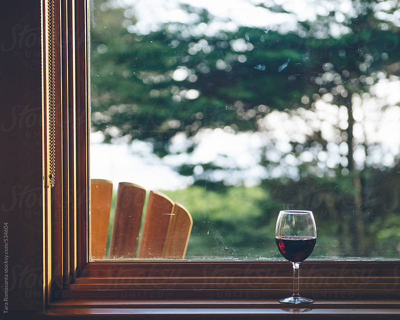 red wine glass sits on a window ledge in a rustic vacation setting by Tara Romasanta for Stocksy United