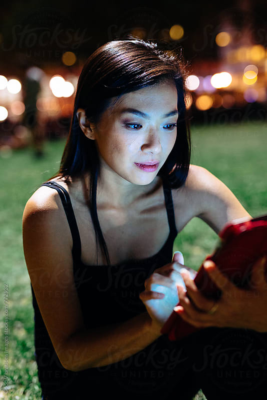 Asian woman using a digital device at night at the park by Good Vibrations Images for Stocksy United