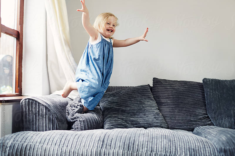 Child jumping onto the couch by sally anscombe for Stocksy United