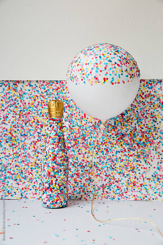 A balloon and a bottle of champagne covered with confetti by Beatrix Boros for Stocksy United