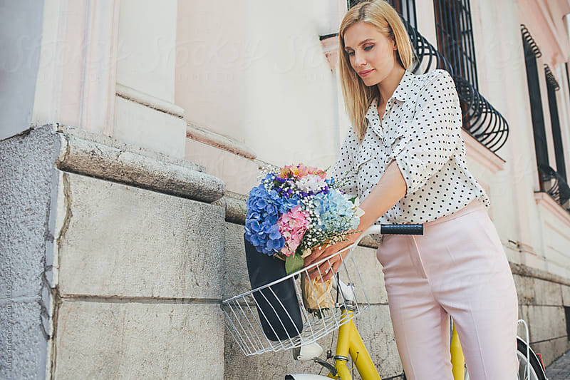 Woman Putting Bouquet in a Bicycle Basket by Lumina for Stocksy United