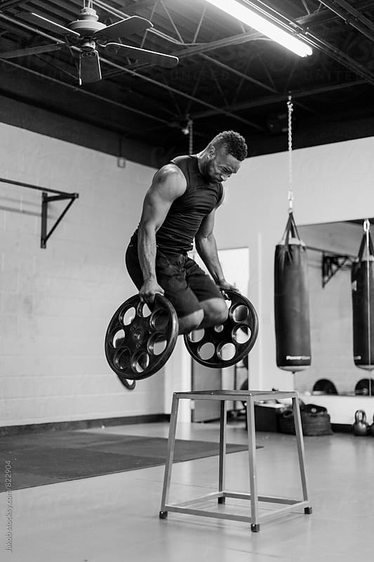 Fit and muscular african american athlete jumping while holding heavy weights by Jakob for Stocksy United