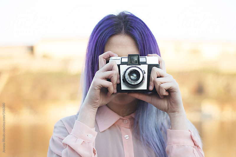 Young girl taking a photo with a retro camera by Jovana Rikalo for Stocksy United