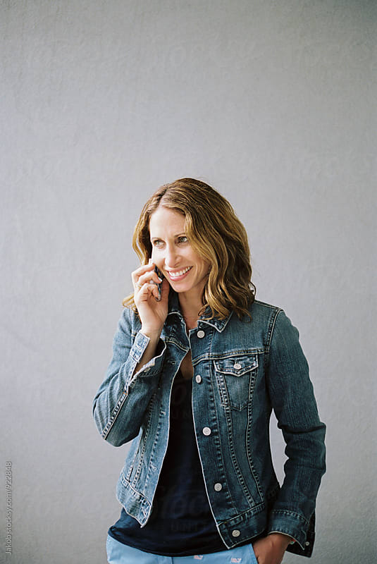 Attractive woman in a denim jacket smiling and talking on the phone by Jakob for Stocksy United