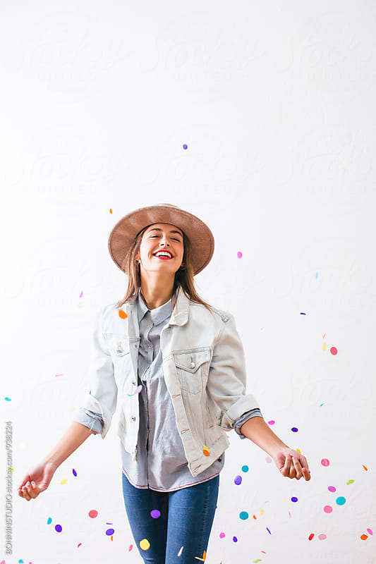 Happy young woman enjoying as confetti falls from above. by BONNINSTUDIO for Stocksy United