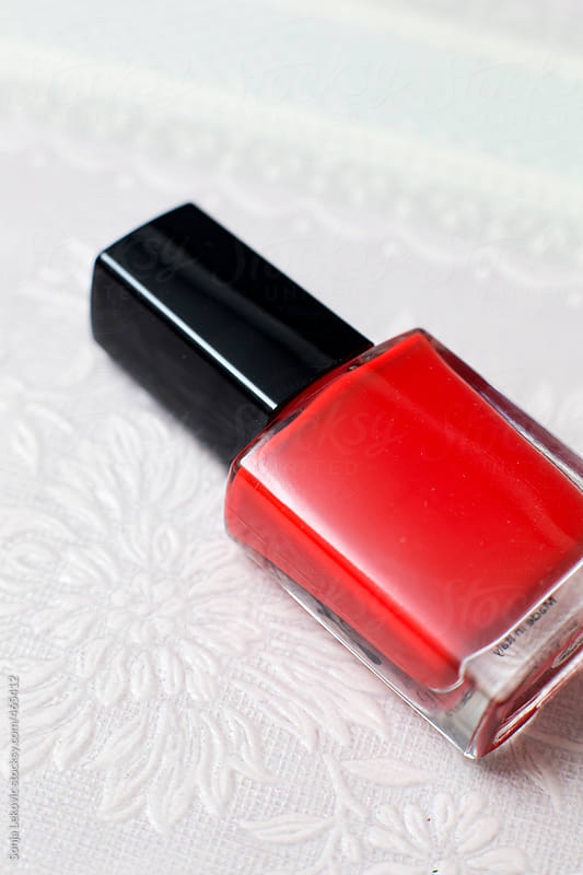 red nail polish on white background by Sonja Lekovic for Stocksy United
