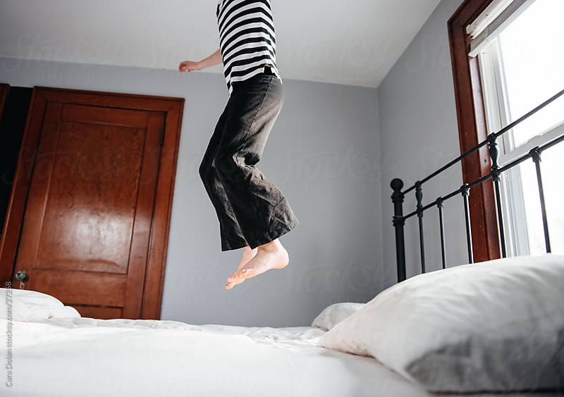 Child jumping on bed by Cara Slifka for Stocksy United