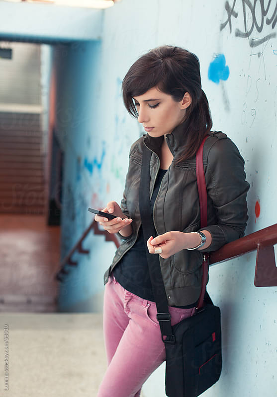 Woman Texting by a Graffiti Wall by Lumina for Stocksy United