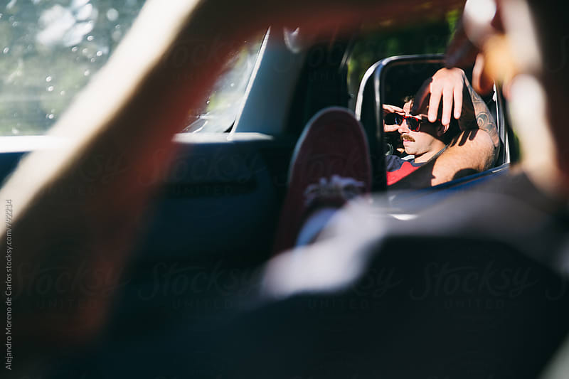 Car mirror view of young man in copilot seat resting while a road trip by Alejandro Moreno de Carlos for Stocksy United