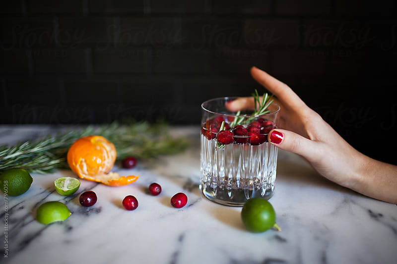 Woman holding a holiday cocktail by Kayla Snell for Stocksy United