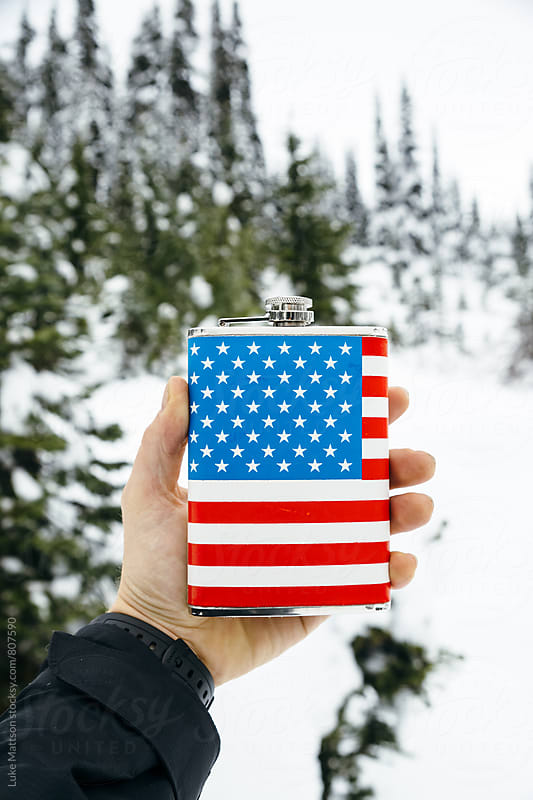 Man Holding Out American Flag Flask In Hand In Snowy Forest by Luke Mattson for Stocksy United