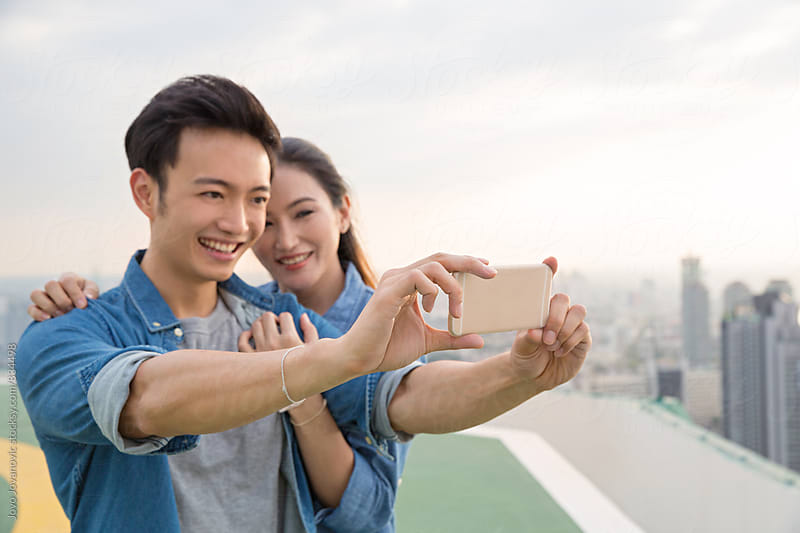 Happy couple taking a selfie on a rooftop by Jovo Jovanovic for Stocksy United