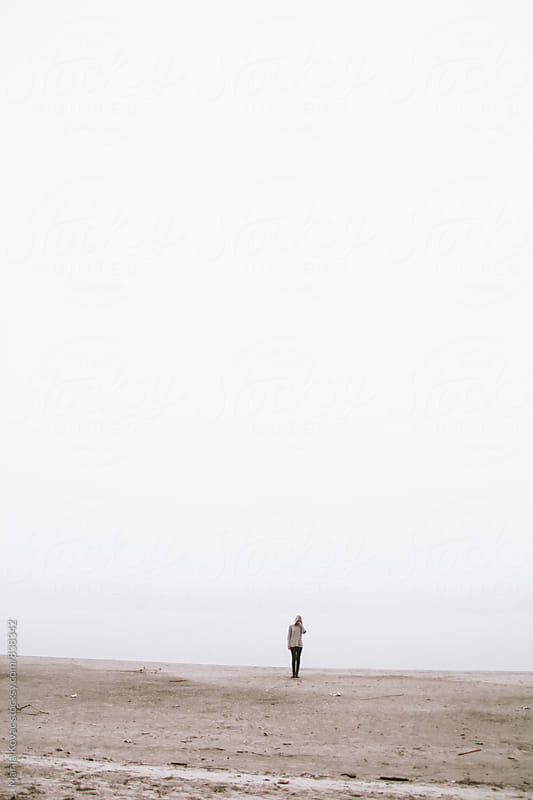 Woman standing on the beach during the fog, vertical by Marija Kovac for Stocksy United