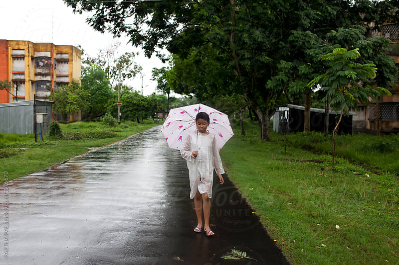 Teenage girl walking in a wet path with white umbrella by PARTHA PAL for Stocksy United