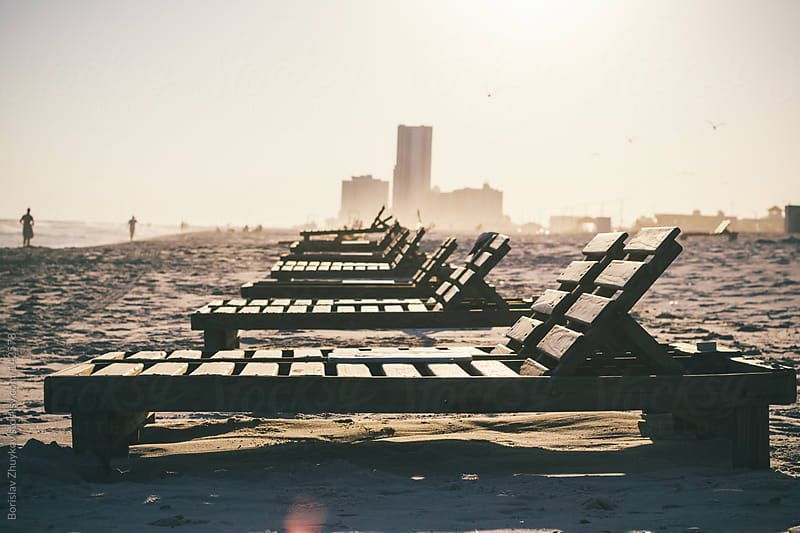 Empty wooden chaise longues on the beach by Borislav Zhuykov for Stocksy United
