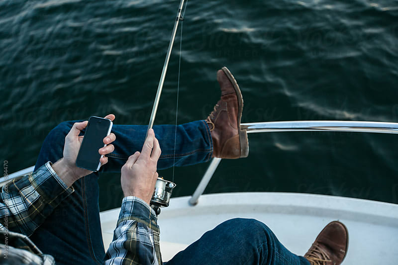 Person fishing on boat holding phone by Matthew Spaulding for Stocksy United