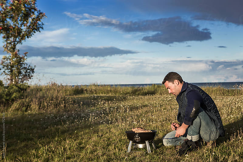 Young man barbecuing in a green field by Lior + Lone for Stocksy United