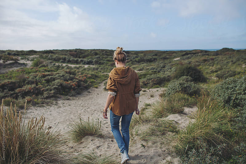 woman walks on sand in the dunes by Denni Van Huis for Stocksy United