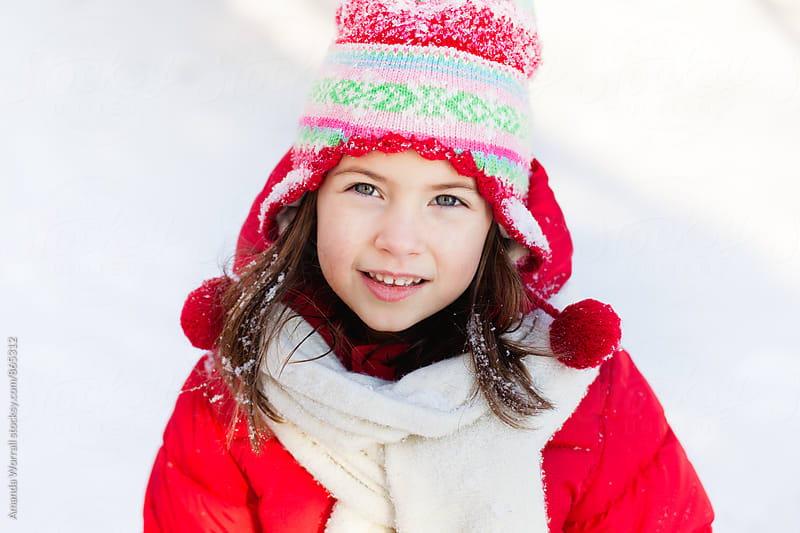 Beautiful young girl wearing red winter gear looking at camera by Amanda Worrall for Stocksy United