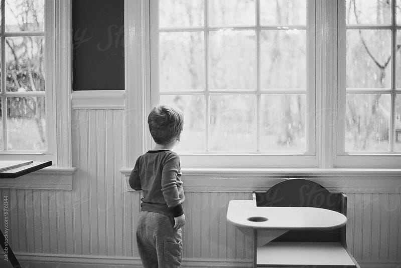 Young boy looking at snow falling outside by Jakob for Stocksy United