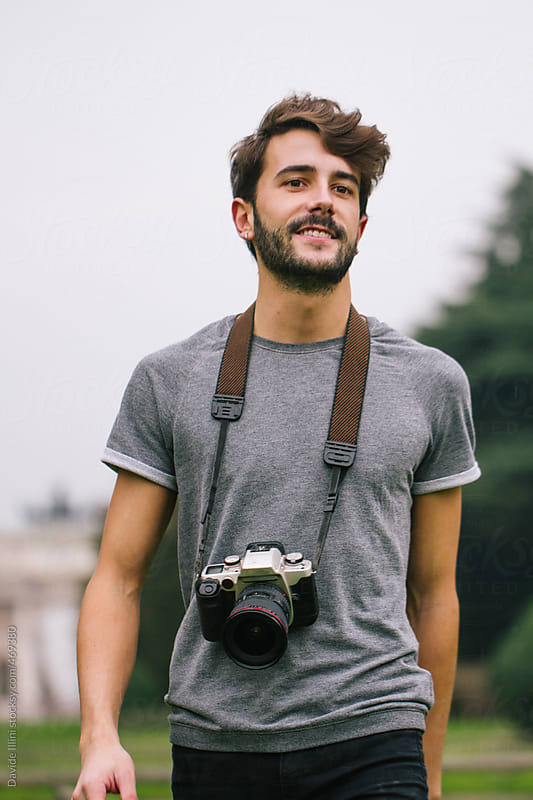 Young man takes pictures at the park with a reflex by Davide Illini for Stocksy United