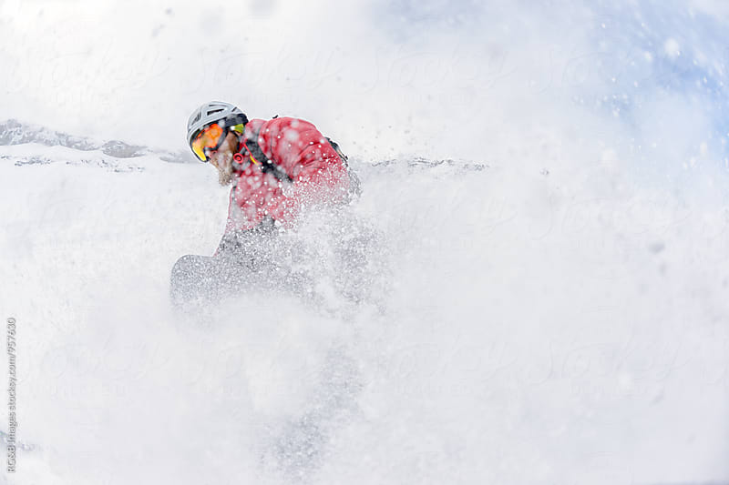 Skier in deep snow, splashing the camera by RG&B Images for Stocksy United