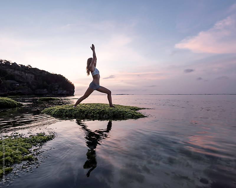 young woman practicing yoga at sunset on a rock in the sea by martin puddy for Stocksy United