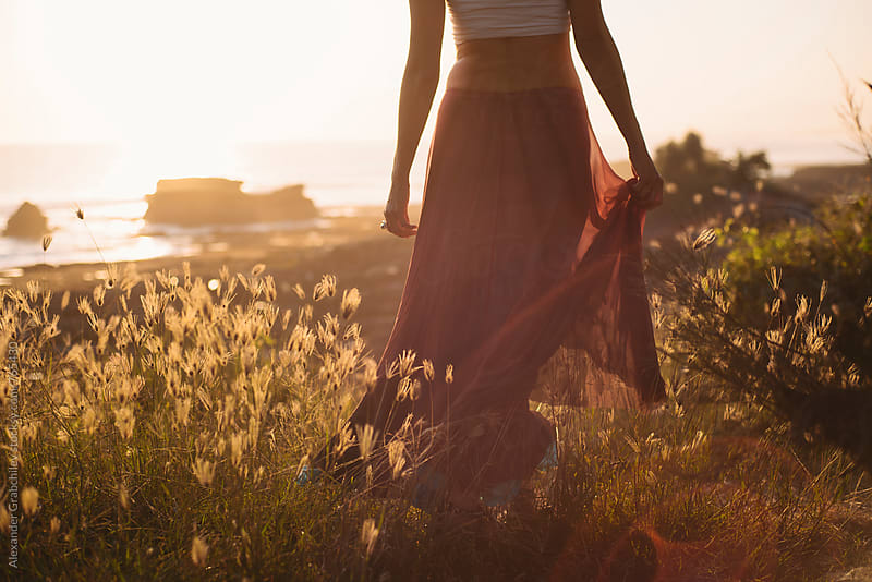 Young Woman Walking In The Grass by Alexander Grabchilev for Stocksy United