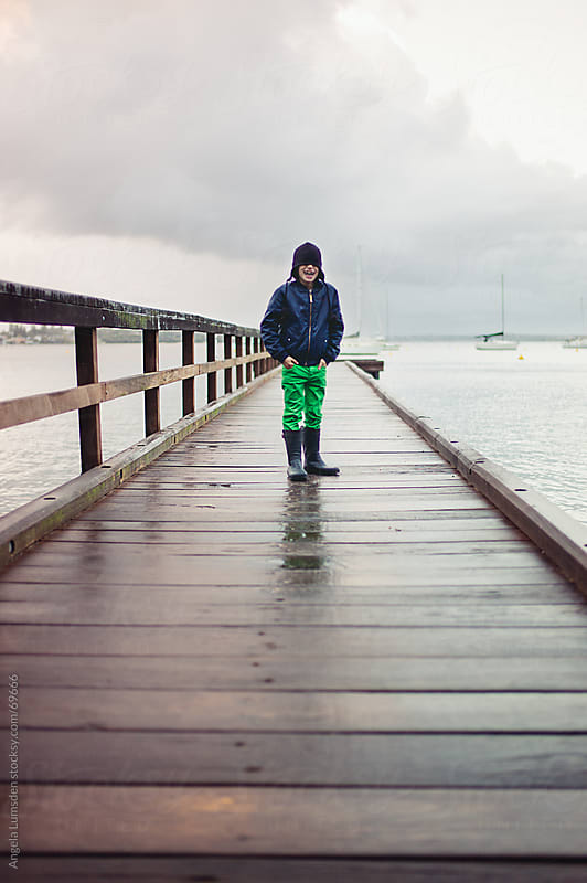 Boy standing on a dock on a rainy day by Angela Lumsden for Stocksy United