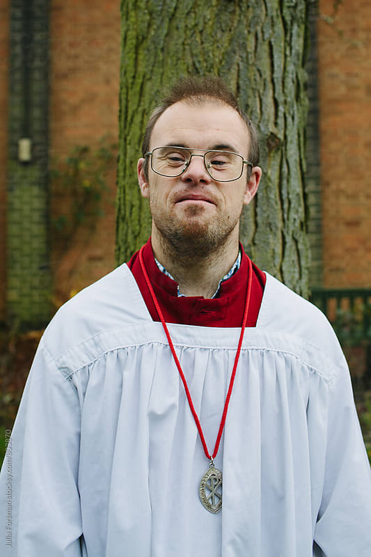 A man with Down's Syndrome wearing altar serving robes by Julia Forsman for Stocksy United