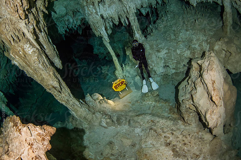 A scuba diver floating with STOP warning board in Mexico's  Cenote Gran by Song Heming for Stocksy United