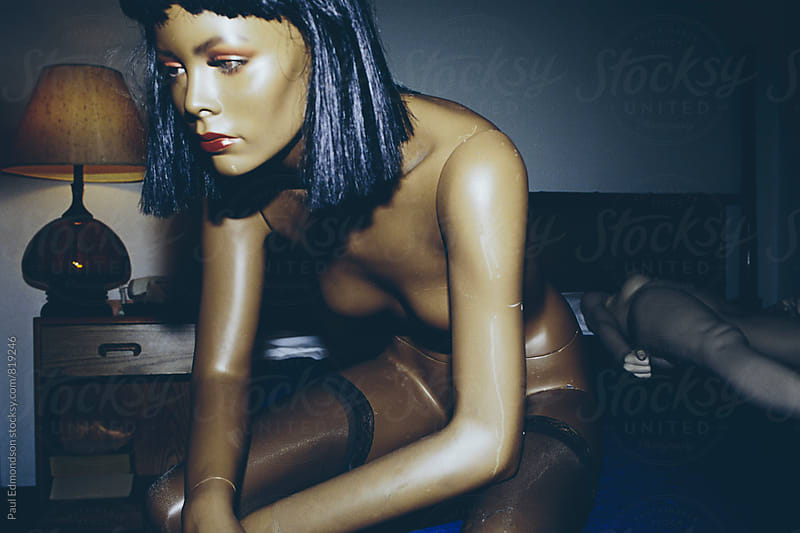 Creepy looking female mannequin sitting on bed with blank expression by Paul Edmondson for Stocksy United