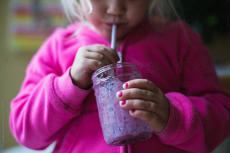 Young girl sips blueberry smoothie with a straw. by Cherish Bryck for Stocksy United