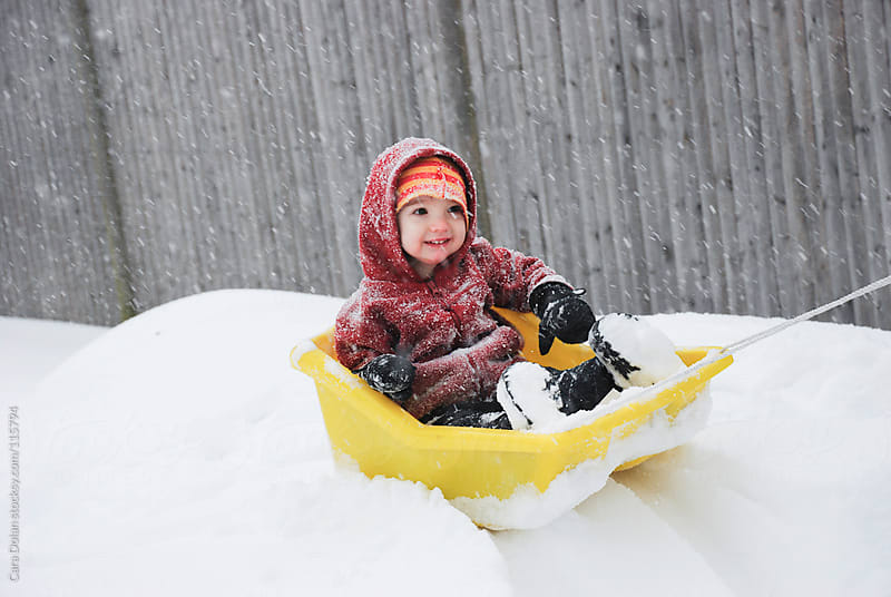 Toddler is pulled on a plastic sled during a snowstorm by Cara Dolan for Stocksy United