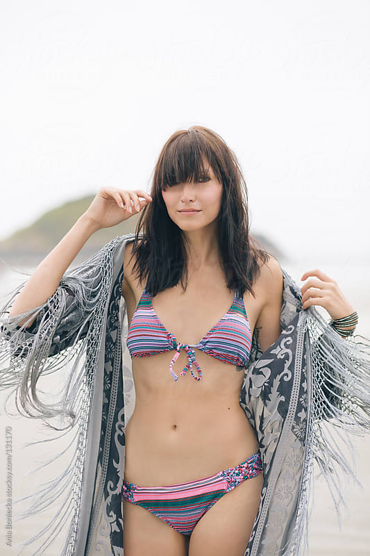 A woman playfully swaying in a pink bikini keeping her fringe kimono from falling off her shoulder by Ania Boniecka for Stocksy United