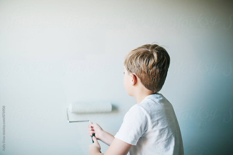 behind a boy painting his bedroom  by Kelly Knox for Stocksy United