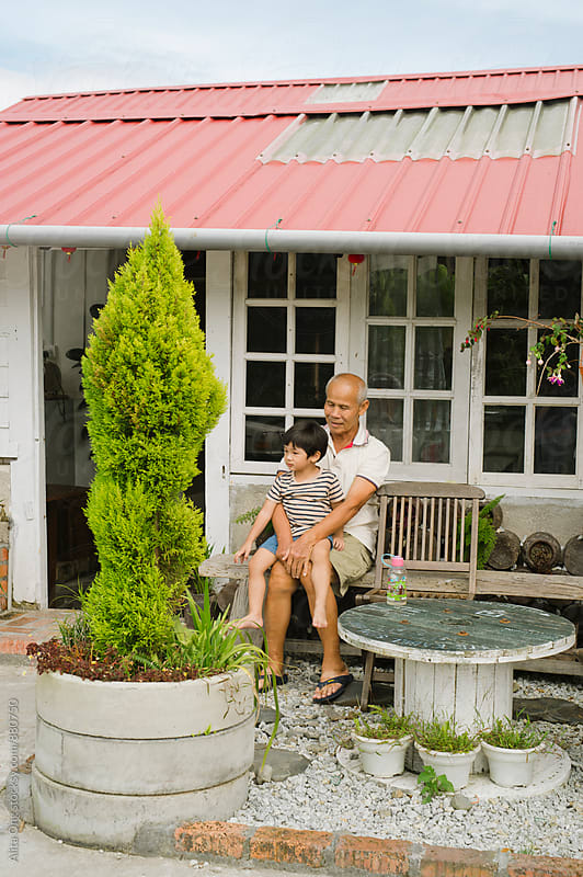 Grandfather and grandson sitting in front of rustic rural home by Alita Ong for Stocksy United