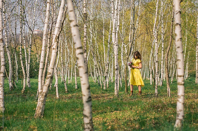 Girl in the yellow dress walking through the forest by Aleksandra Jankovic for Stocksy United