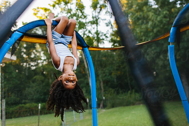 A young girl hanging upside down on a trampoline by Kristen Curette Hines for Stocksy United