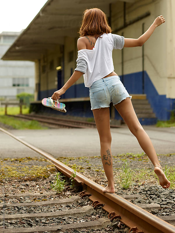 Girl balancing on tracks by Simon Bolz for Stocksy United