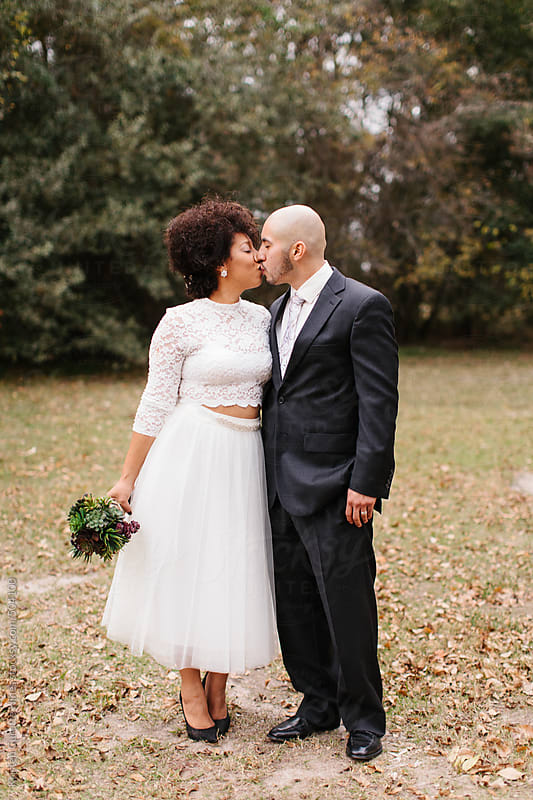 Bride and groom kissing in nature. by Kristen Curette Hines for Stocksy United