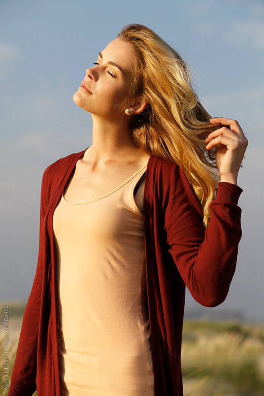 young woman enjoying the last rays of sun by Rene de Haan for Stocksy United