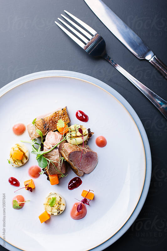 Duck breast with potato rosti,charred leeks,rhubarb puree,carrots and tayberry jelly. by Darren Muir for Stocksy United