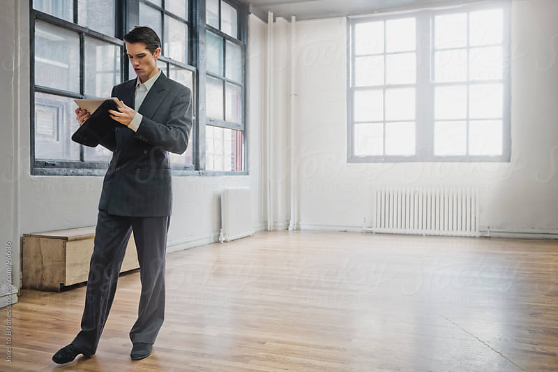 Man in Suit Using Tablet Device in Empty Old Room by Joselito Briones for Stocksy United